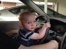 a baby sits on his dad's lap in the driver's seat of a car