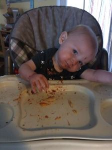 a baby sits in a high chair, resting his head on his arm. He is covered in tomato sauce.
