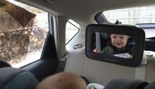 a baby smiles at his reflection in a mirror from his carseat