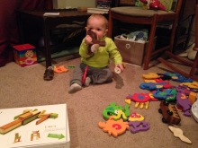 a baby sits in the middle of a room, toys scattered everywhere around him