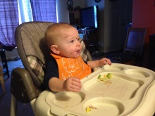 A baby sits in a highchair, looking off camera for more food.