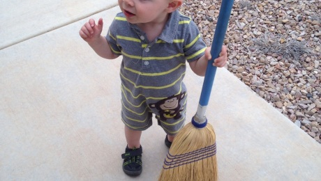 A young boy holds a tall broom, sweeping a porch